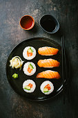 Sushi with avocado and salmon served on black plate with soy sauce on dark vintage table.