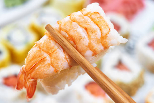 Sushi set. Chopsticks with portion of sushi stock photo