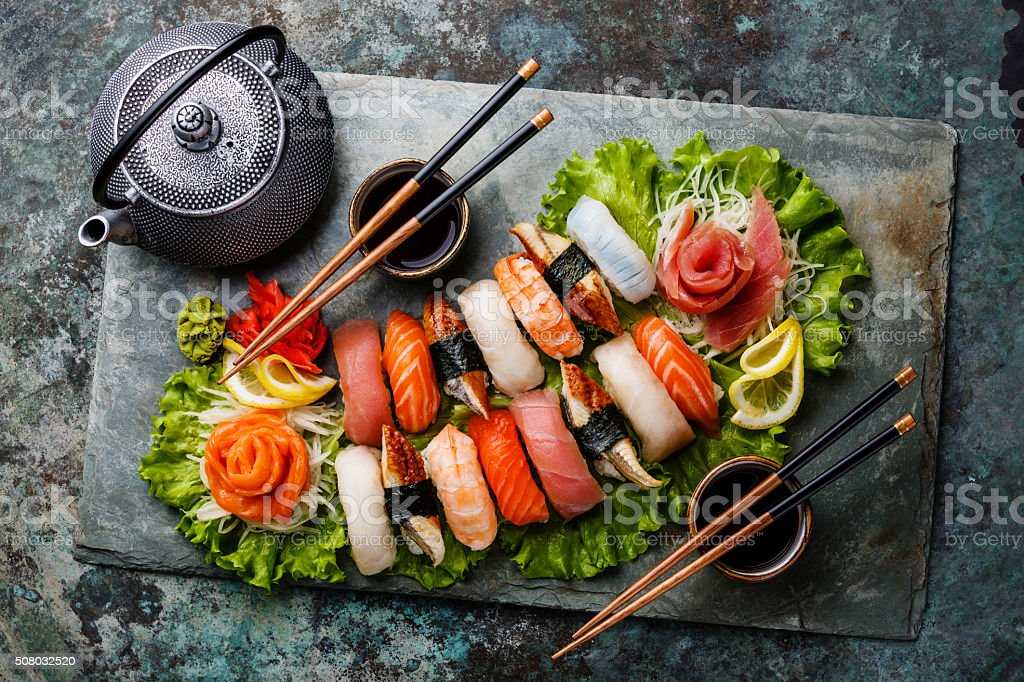 Sushi Set nigiri and sashimi with tea Sushi Set nigiri and sashimi with tea served on gray stone slate on metal background Chopsticks Stock Photo