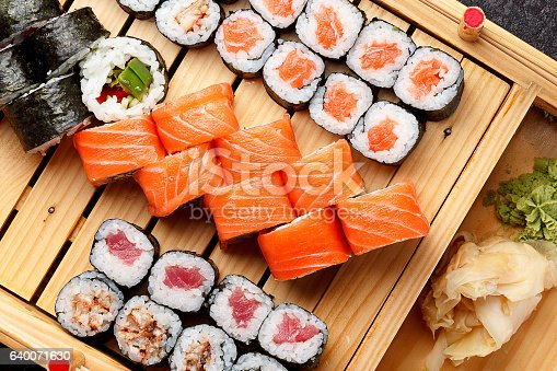 istock Sushi set on a wooden plate and dark concrete background. 640071630