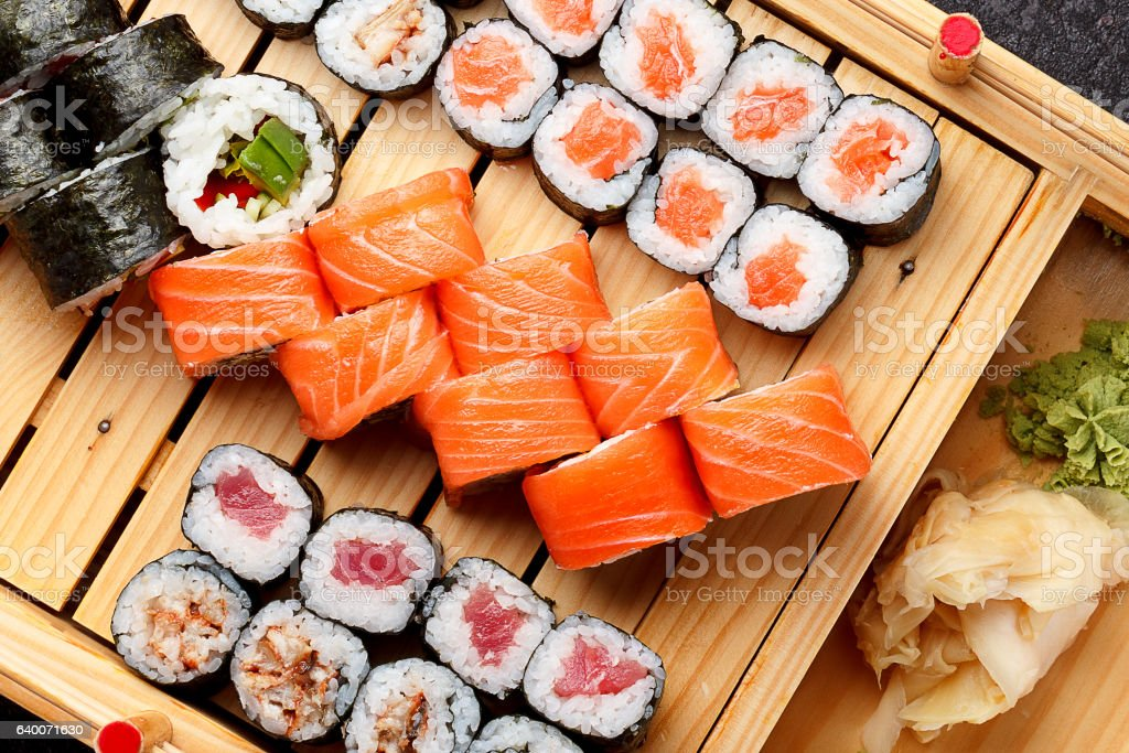Sushi set on a wooden plate and dark concrete background. - Photo