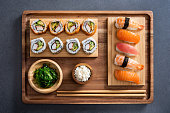 Top view of delicious variety sushi pieces setting on wooden tray. High angle view of japanese food with huramaki, maki, rolls, nigiri, seaweed and rice in a bowl. Flat image of fresh japanese sushi served on bamboo tray with chopstick on slate table.