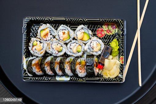 Flat lay Sushi rolls and chopsticks on dark background.