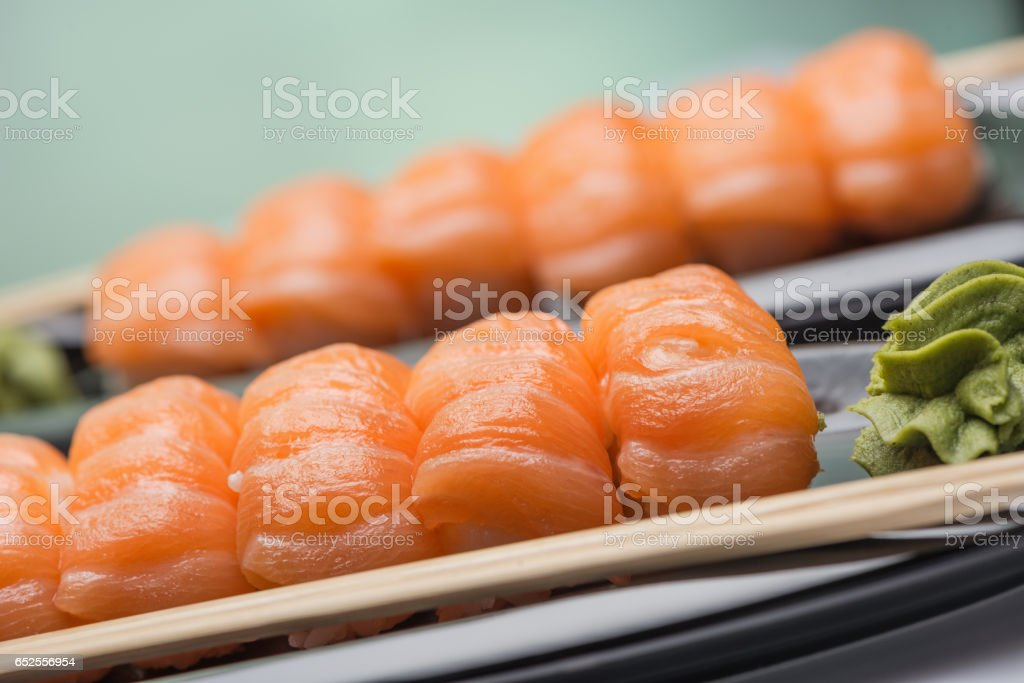 Sushi with a light-salted salmon, wooden sticks and sauce of wasabi on a ceramic dark plate стоковое фото