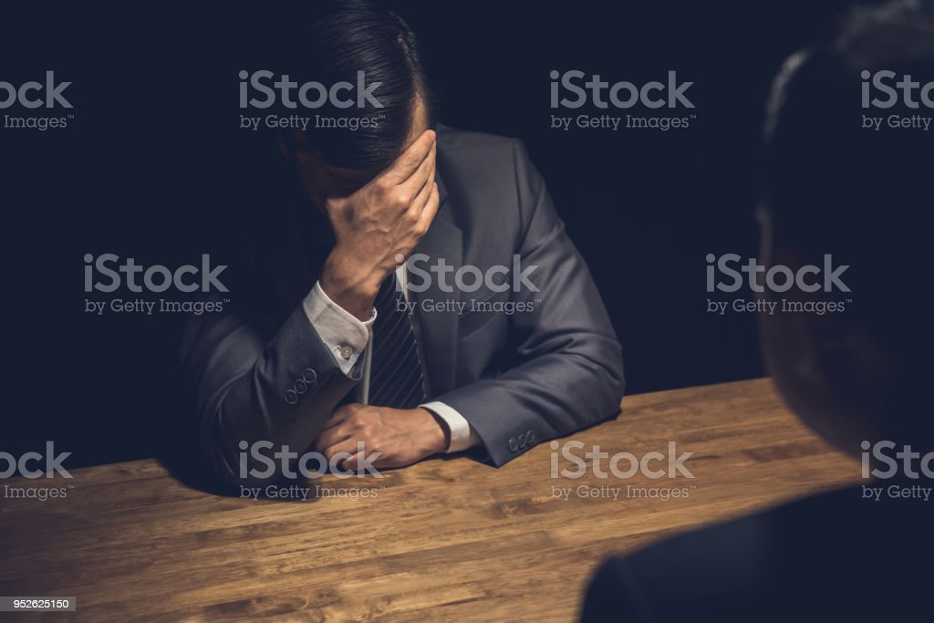 Suspect businessman displaying regret  in dark interrogation room stock photo