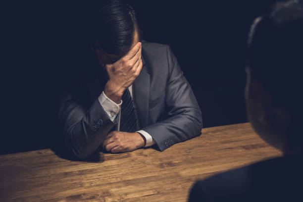 suspect businessman displaying regret  in dark interrogation room - victim stock pictures, royalty-free photos & images