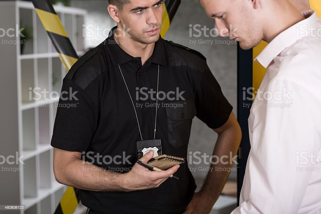 Suspected man talking with policeman stock photo