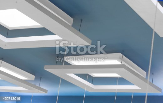 white suspended ceiling  with lights on a blue coloored ceiling
