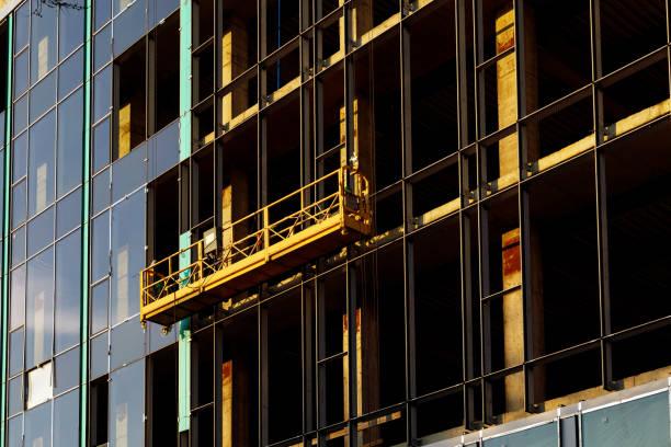 Aufgehängte Baukrippe in der Nähe der Wand des Hochturmgebäudes mit belüfteter Fassade auf der Baustelle. Engineering urbanen Hintergrund – Foto