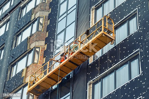 istock Suspended construction craddle near wall of hightower residentaial building with insulation and ventilated facade on construction site. Engineering urban background 1347658742
