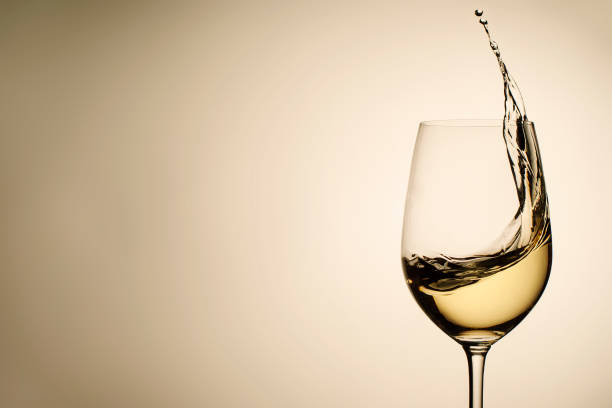 Suspended drops and splash of white wine in glass stock photo