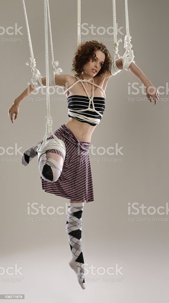 Suspended Fashion Model Puppet Hanging on White Ropes stock photo
