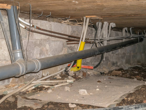 Suspended foundation under old house is often called crawl. Pipes for drain, sewer, water and electricity. stock photo