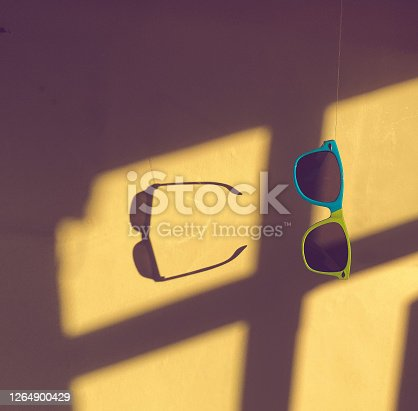 Suspended Shades - sunglasses hanging from above with the sunlight creating a beautiful window collage and a shadow.