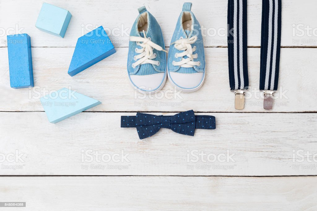 Suspenders, a bow tie and blue shoes for a boy. view from above stock photo