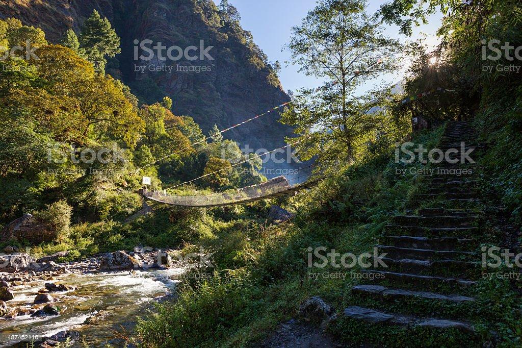 Suspension bridge above mountain canyon river. stock photo