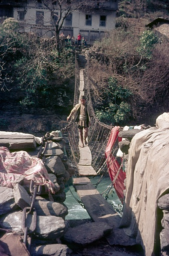 Nepal, 1977. A man crosses a suspension bridge in Nepal. Furthermore: people in the background.
