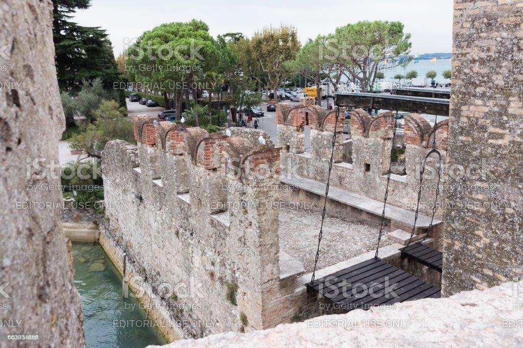 Suspension bridge of Castello Scaligero through the water in Sirmione stock photo