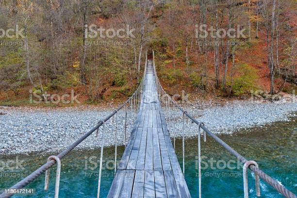 Photo of Suspension bridge over a mountain river going into the autumn forest