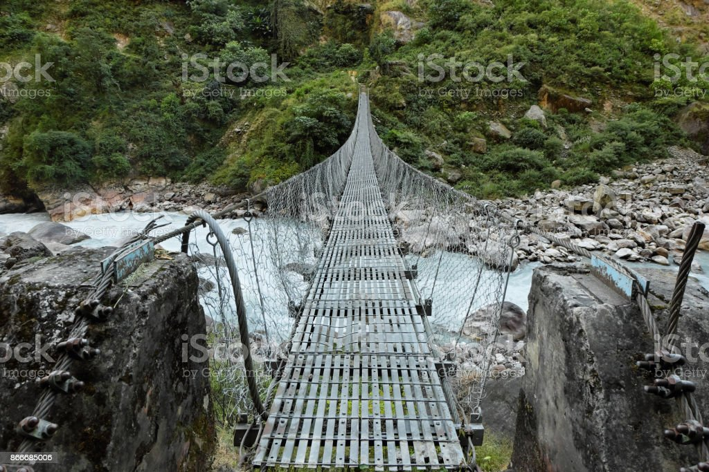 Suspension bridge over the rough mountain river in Nepal stock photo