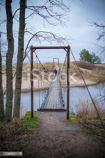 a small suspension bridge across the river, view along the bridge, dramatic picture of nature, high resolution photo, full frame,