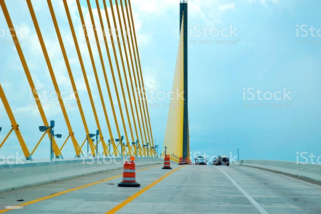 Suspension Bridge Vivid Yellow Ties on Highway Against Cloudy Sky royalty-free stock photo