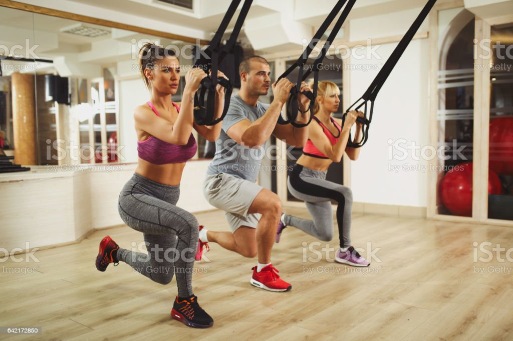 TRX suspension training- people doing arm and leg exercises stock photo