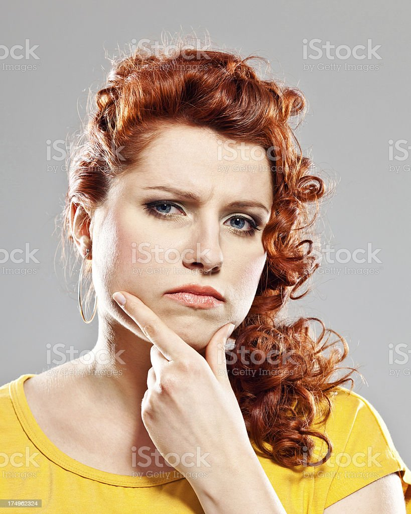Suspicion Portrait of worried young woman looking at camera with hand on chin. Studio shot. 20-24 Years Stock Photo