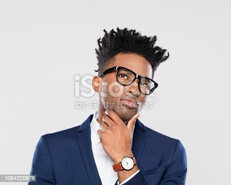 611876426 istock photo Suspicious african businessman looks up doubtfully 1064220976