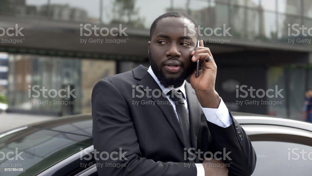 Verdächtige schwarzer Mann nervös sprechen am Telefon, Verschwörung gegen Regierung - Lizenzfrei Abwarten Stock-Foto