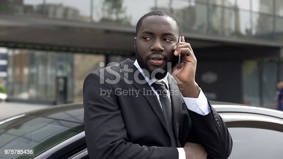 istock Suspicious black man nervously speaking on phone, plotting against government 975785436