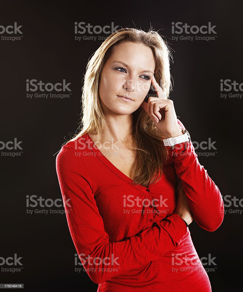 Suspicious blonde in red dress considers something seriously stock photo