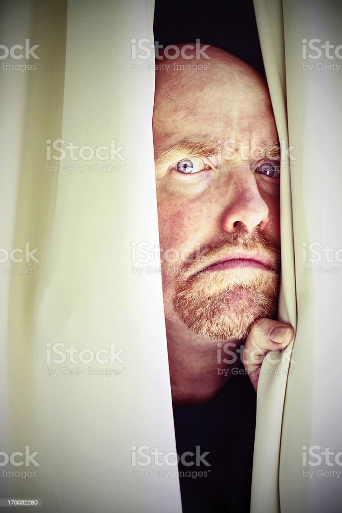 Suspicious, frowning man peers sideways through closed curtains stock photo
