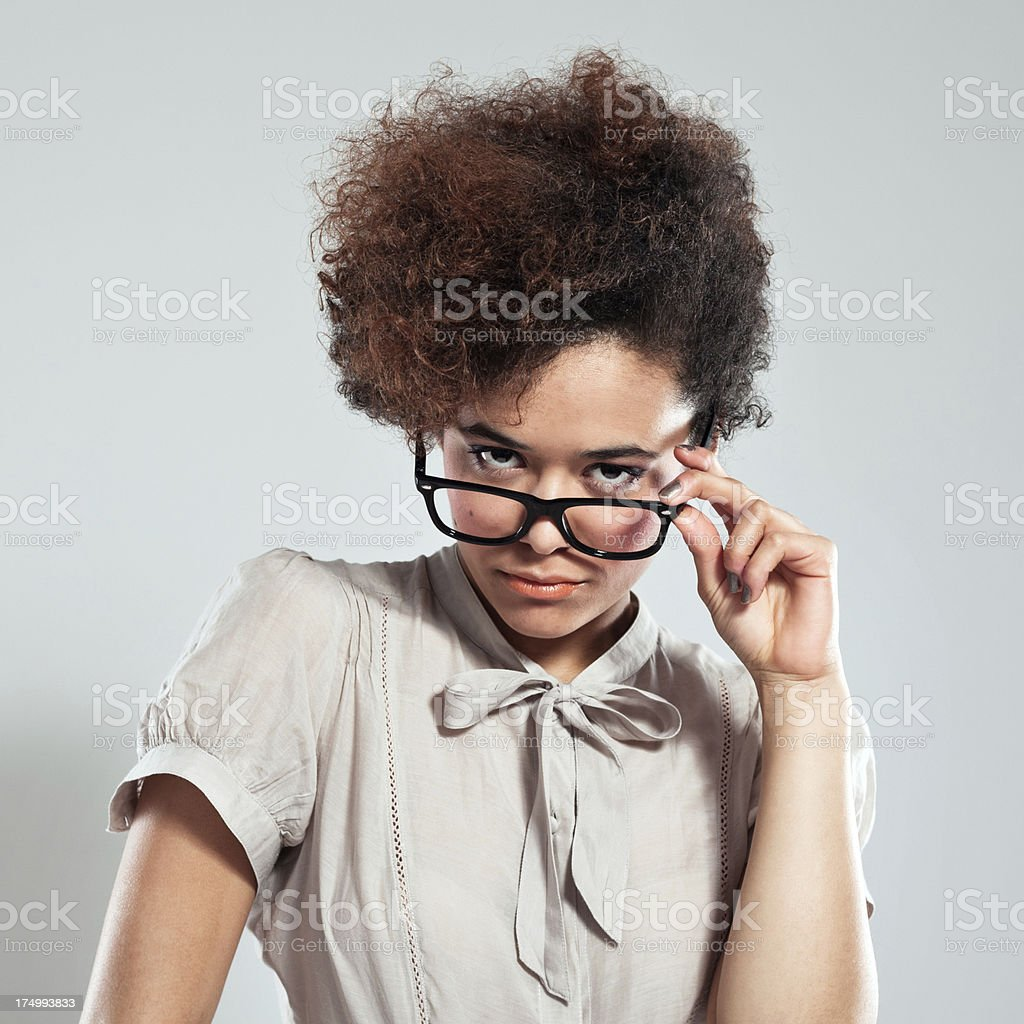 Suspicious Girl Portrait of cute teenaged afro girl wearing nerd glasses, standing against grey background and looking at the camera. 18-19 Years Stock Photo
