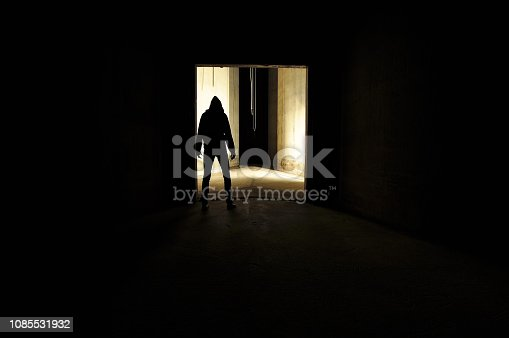 unrecognizable silhouette of person with a hood standing in a door way of an empty concrete room.