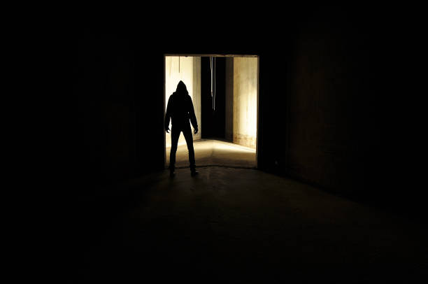 verdacht uitziende silhouet van hooded persoon in de deuropening. - moordenaar stockfoto's en -beelden