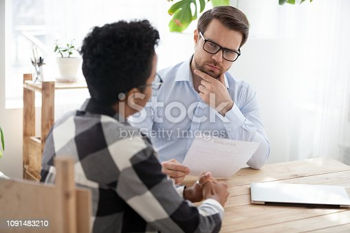 istock Suspicious male employer doubt about black applicant candidature 1091483210