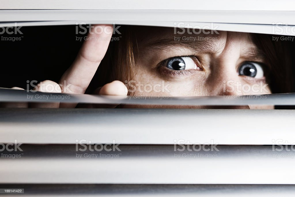 Suspicious nervous young woman peeps through venetian blinds stock photo