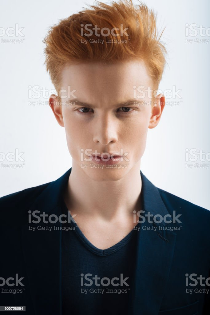 Suspicious red-headed young man staring stock photo