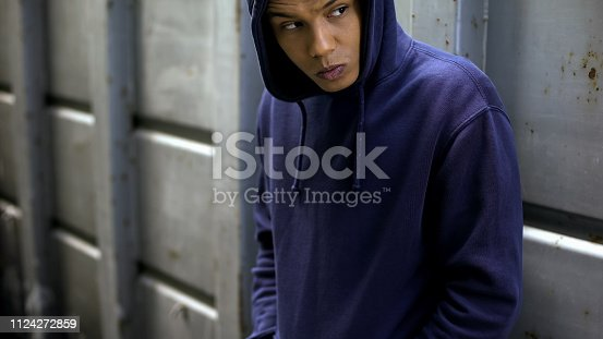 istock Suspicious teenager hiding and looking around, secretly selling drugs, trading 1124272859