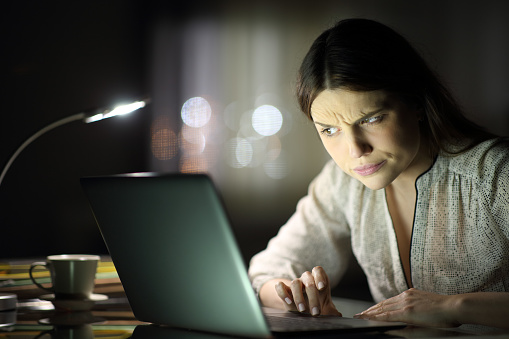 Suspicious woman checking laptop content in the night