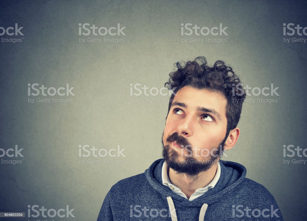 Suspicious young man looking up stock photo