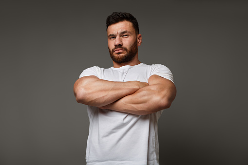 Suspicious young man with crossed big muscular arms