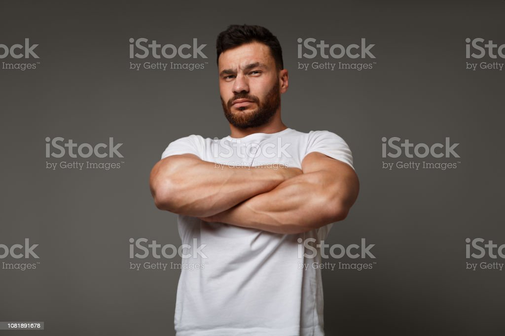 Suspicious young man with crossed big muscular arms stock photo
