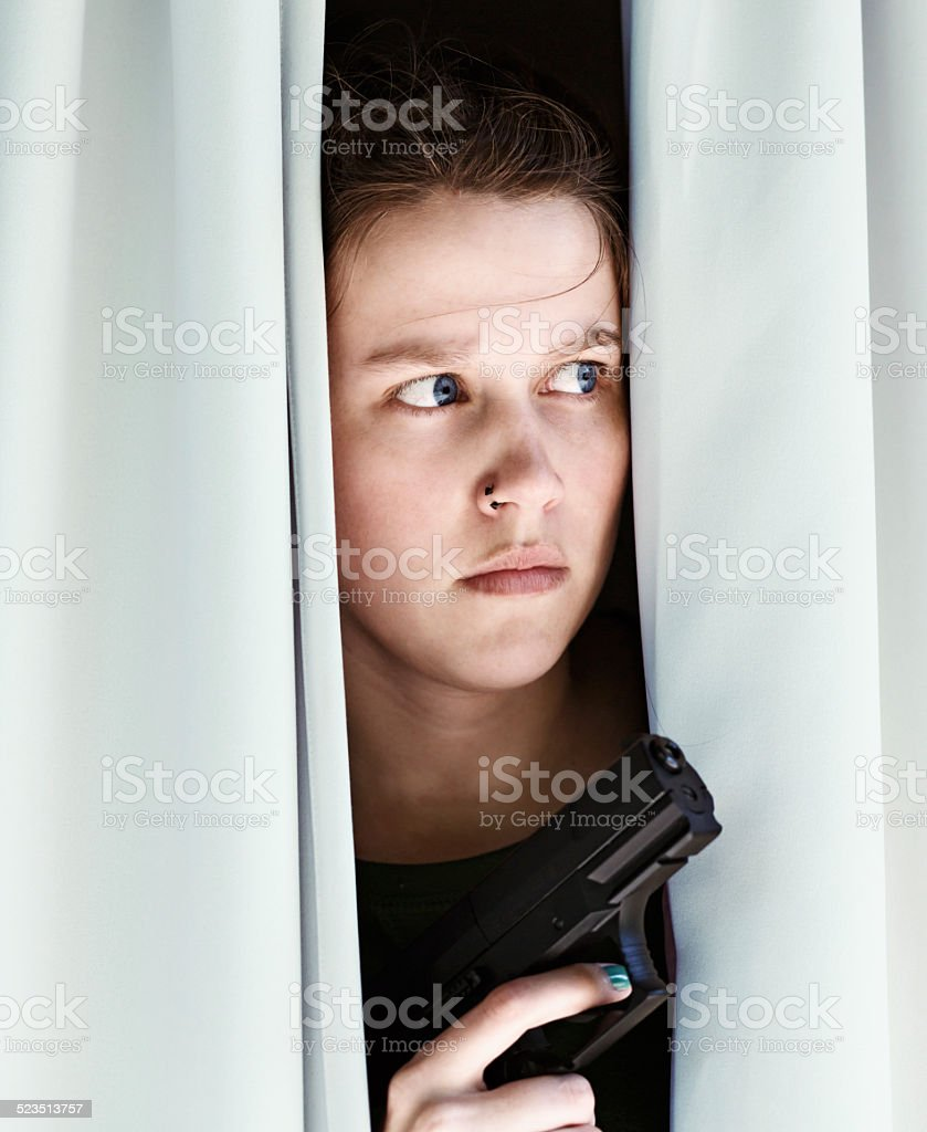Suspicious young woman behind curtains is armed, will defend herself stock photo