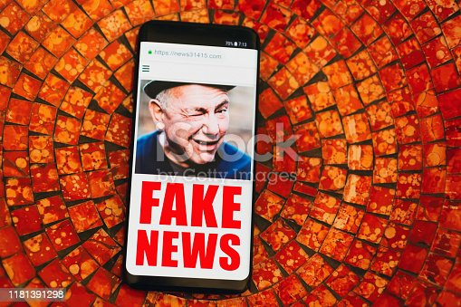 A dodgy looking man wink from a smart phone app headlined Fake News.  Please note: The screen content is a dummy designed by me. The picture is mine. The URL is generic and unique, containing the first five digits of pi. Thanks.