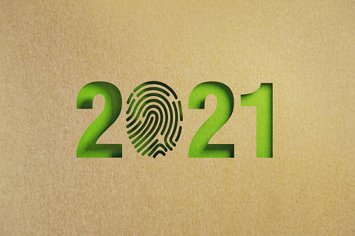Cut out fingerprint shape made of recycled paper form 2021 green background. Horizontal composition with copy space. Sustainability concept.