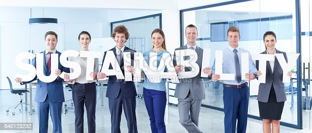 Business men and business women standing in office and holding letter. Sustainability.