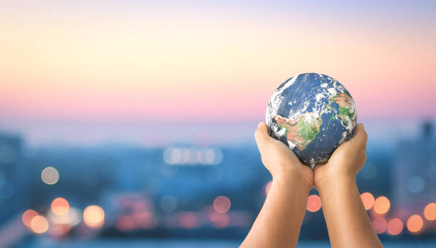 Sustainable community concept Human hands holding earth global over blurred city night background. Elements of this image furnished by NASA environment stock pictures, royalty-free photos & images