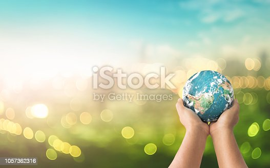 Human hands holding earth global over blurred green nature background. Elements of this image furnished by NASA